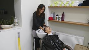 Parrucchiere che lava i capelli dei clienti in un bacino moderno nel suo salone di lavoro di parrucchiere come prepara disegnare  stock footage