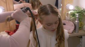 Parrucchiere che per mezzo delle tenaglie dei capelli per lo studio d'arricciatura di bellezza dell'adolescente della ragazza stock footage