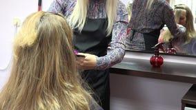Parrucchiere che pettina i capelli femminili del cliente davanti allo specchio Cambiamento del fuoco 4K stock footage