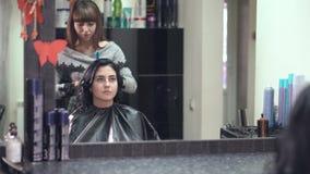 Parrucchiere che pettina i capelli in un salone di bellezza video d archivio