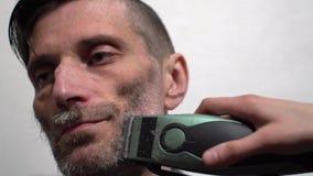 Parrucchiere che rade barba dell'uomo attraente in parrucchiere stock footage