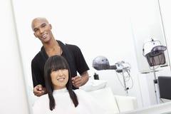 Parrucchiere con il cliente femminile al salone di bellezza immagini stock