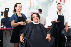 Parrucchiere con il cliente nel salone di bellezza Fotografia Stock