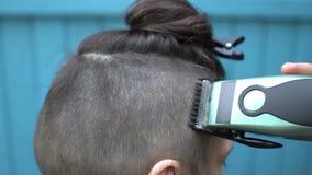 Parrucchiere femminile che fa taglio di capelli maschio con la tosatrice nel salone di lavoro di parrucchiere sulla fine di vista video d archivio