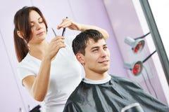 Parrucchiere femminile sul lavoro che fa taglio di capelli fotografia stock
