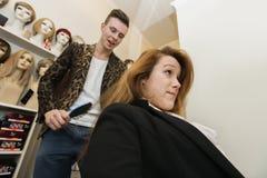 Parrucchiere maschio che spazzola i capelli del cliente femminile in salone fotografie stock