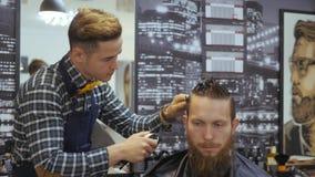 Parrucchiere per gli uomini barbershop Cura di capelli Il parrucchiere con un taglio di capelli lavora per un'acconciatura per un stock footage