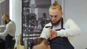 Parrucchiere per gli uomini barbershop Il parrucchiere con un taglio di capelli lavora per un'acconciatura per un giovane tipo Un archivi video