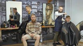 Parrucchiere per gli uomini barbershop Preoccupandosi per la barba Il parrucchiere con un taglio di capelli lavora per un'acconci stock footage