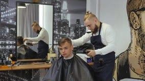 Parrucchiere per gli uomini barbershop Un giovane tipo ottiene un servizio di cura di capelli e di taglio di capelli da un uomo b archivi video