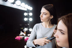Parrucchiere piacevole serio che per mezzo di un raddrizzatore dei capelli Fotografia Stock Libera da Diritti