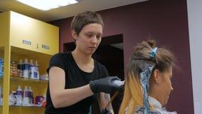 Parrucchiere professionista che fa acconciatura per la giovane donna graziosa video d archivio