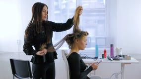 Parrucchiere professionista che fa acconciatura per la giovane donna graziosa con capelli lunghi stock footage