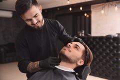Parrucchiere professionista che prepara cliente alla rasatura immagine stock