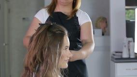 Parrucchiere professionista, stilista che colora i capelli teenager della ragazza stock footage