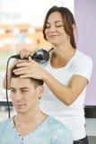 Parrucchiere sul lavoro che fa taglio di capelli fotografie stock