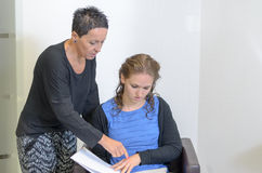 Parrucchiere Woman Explaining ad un cliente femminile Immagine Stock Libera da Diritti