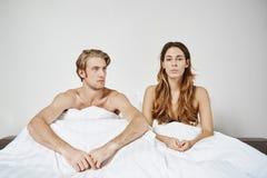 Parsammanträde i säng under filten som har frågor i sovrummet som uttrycker besvikelse Par hade kamp i morgon och arkivfoto