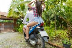 Parsammanträde på bakre sikt för motorcykelbaksida, härlig tillfällig man och kvinnarittmopeden på vägen i tropisk skog Royaltyfria Foton