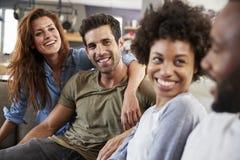 Parsammanträde på Sofa With Friends At Home samtal royaltyfria bilder