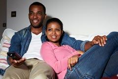 Parsammanträde på Sofa Watching TV tillsammans arkivbild