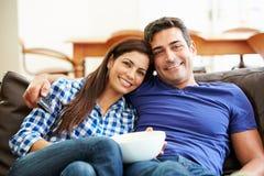 Parsammanträde på Sofa Watching TV tillsammans royaltyfri fotografi