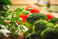 Parsley and broccoli with tomatoes in the background.  stock image