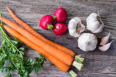 Parsley, Carrots, Radishes, and Garlic. Parsley, three carrots, three radishes, three garlic and two cloves of garlic on a old wooden table. Top view Royalty Free Stock Photos