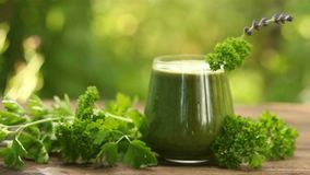 Parsley and celery juice in glass on wooden table stock footage