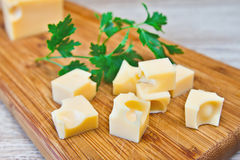 Parsley and cheese on a wooden board. Parsley and the pieces of the cheese on a wooden board Stock Image
