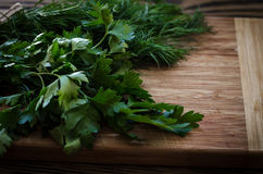 Parsley and dill on a cutting board, wooden background Stock Photo