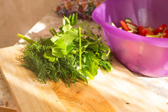 Parsley and dill on wooden cutting board. Preparation of vegetab Royalty Free Stock Photo