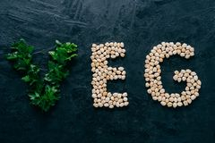 Parsley and dry garbanzo in form of letters meaning veg, vegetarian isolated over dark background. Organic protein product. Vegan. Food stock image
