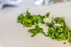 Parsley and garlic on wooden cutting board, cooking time backgro Stock Photo