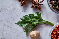 Parsley, nutmeg and anise star on white textured background, top view, close-up, selective focus. Scented condiment. Aromatic spices. Exotic ingredient. Indian Royalty Free Stock Photography