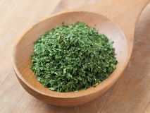 Parsley seasoning in a wooden spoon. Stock Photos