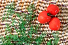 Parsley and tomato on bamboo plate. Parsley and tomato are widely cultivated as an herb, a spice and a vegetable, it is ingredient in many menu of Thai's food royalty free stock photography