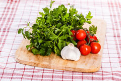 Parsley tomatoes and garlic on a cloth Stock Image