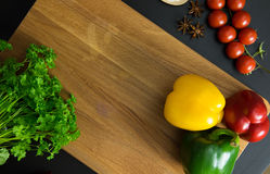 Parsley tomatoes and red green yellow peppers. Parsley, tomatoes, and peppers on clean wood backgorund Stock Image