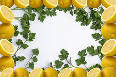 Parsley on White Tablecloth and Lemon Frame. Green Parsley and Lemon Frame on White Tablecloth Background Royalty Free Stock Images