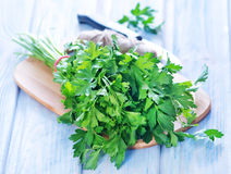 Parsley. On wooden board and on a table stock photography