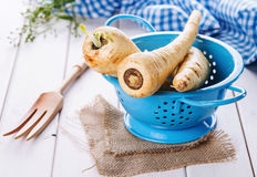 Parsnip in a blue colander over white wooden background Royalty Free Stock Image