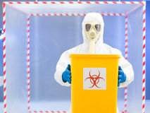 Parson in protective suit holding biohazard waste. Person wearing a protective suit and gas mask holding a yellow garbage bin marked as bio hazardous with both Royalty Free Stock Photos