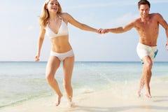 Parspring till och med vågor på strandferie Royaltyfria Bilder