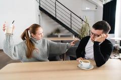 Parstridighet i morgonen Kvinnan kastar ett exponeringsglas på hennes man Barnpar som grälar och att ropa arkivfoton