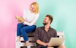 Parstudenter med att studera för bok och för bärbar dator Modernt studerande digitalt i stället omodernt för inställning Man- och royaltyfria bilder
