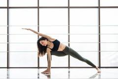 Parsvakonasana Красивая практика женщины йоги около предпосылки студии комнаты йоги окна Концепция йоги стоковое фото