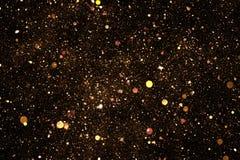Partículas de oro de las burbujas de la chispa del brillo en el fondo negro, día de fiesta festivo de la Feliz Año Nuevo del even Foto de archivo libre de regalías