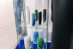 Partículas plásticas en los frascos de cristal El polímero granulado plástico del color Plástico reciclado machacado in vitr fotos de archivo