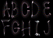 Part of alphabet freezelight. Bright rainbow letters, part of english alphabet on black background. Isolated stock illustration